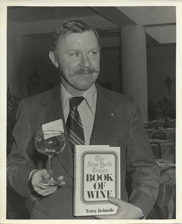 Photo of Terry Robards holding a wine glass and book